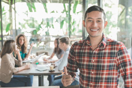 Jeune ouvrier se réunit dans un café avec son travail d'équipe Banque d'images - 83124836