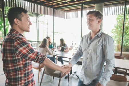 two young male business partner shake hand in a cafe