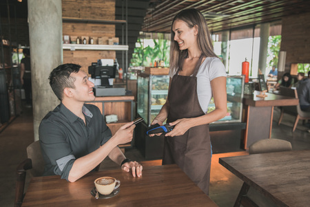 customer paying his bills using credit card, assisted by waitress photo
