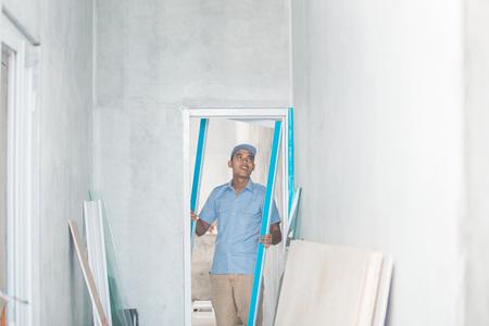 Portrait of young Asian worker installing doors Stock Photo