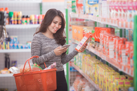 happy young asian woman shopping at supermarket with check list on her mobile phone Stockfoto
