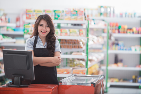 portrait of young attractive woman at cash register in a store