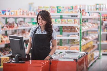 Portret van glimlachend Aziatisch vrouwelijk personeel die zich bij contant geldteller in supermarkt bevinden