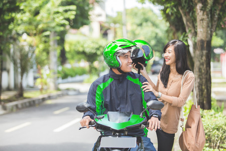 Happy commercial motorcycle taxi driver taking his passenger to her destination Stock Photo
