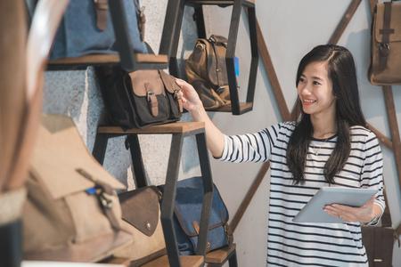 店のオーナーが彼女のバッグ店でタブレット pc を使用して