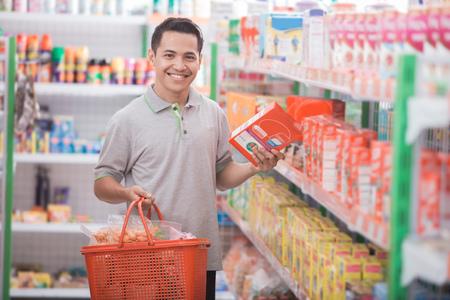 Aziatische man koopt wat spullen bij supermarkt