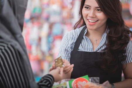 portrait of happy woman paying her shopping with credit card in grocery store Standard-Bild
