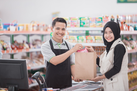 happy muslim woman buying product at grocery store or supermarket