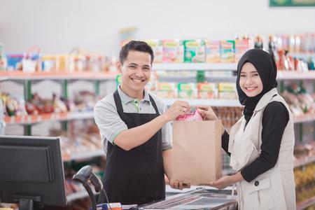 Gelukkig moslimvrouw het kopen product bij kruidenierswinkelopslag of supermarkt Stockfoto - 84486457