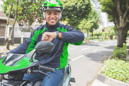heureux l & # 39 ; homme assis sur sa moto et en regardant sa montre