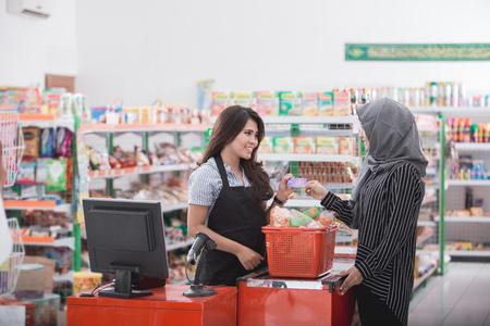 슈퍼마켓에서 점원 신용 카드로 그녀의 청구서를 지불하는 여성 고객