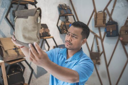 man checking the quality of the product at bag store