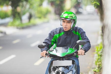 Retrato de hombre asiático trabajo como conductor profesional de motociclista comercial Foto de archivo