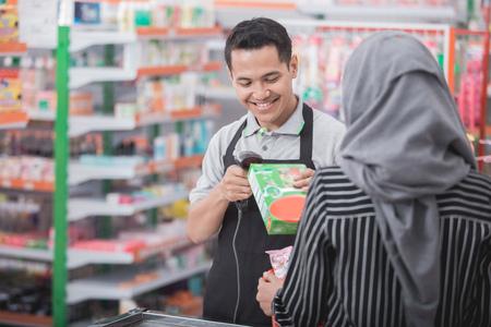 男性店主のスーパー マーケットで商品のバーコードをスキャン