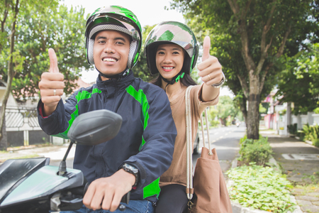 Happy commercial motorcycle taxi driver and his passenger showing thumb up to camera