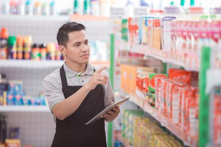 Commerçant asiatique masculin travaillant dans une épicerie Banque d'images - 84485787