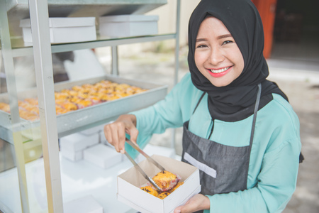 portrait of young happy female muslim working as street food seller, selling fresh cake