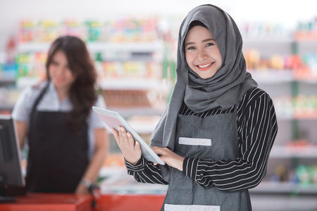portrait of young attractive muslim woman with tablet pc in a store