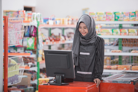 muslim female working as a cashier at supermarket Reklamní fotografie - 84486485