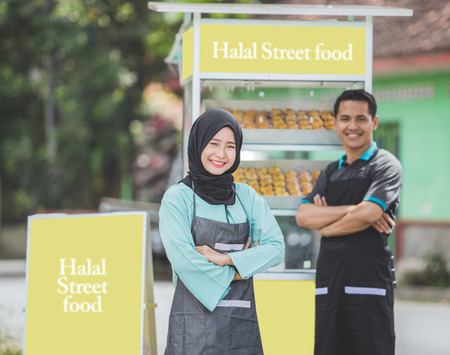young asian muslim small food stall owner, standing proudly with her partner at the background. halal street food concept Stock Photo