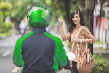 portrait of woman standing on a sidewalk ordering motorcycle taxi by waving her hand Stock Photo