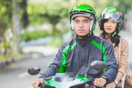 Professional motorcycle taxi driver taking a passenger to her destination Stock Photo