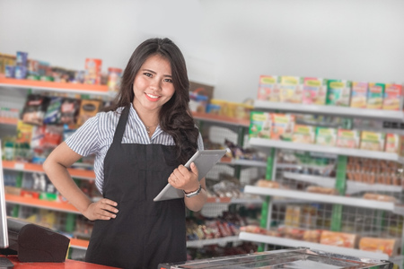 Portrait of young attractive woman with tablet computer in a store