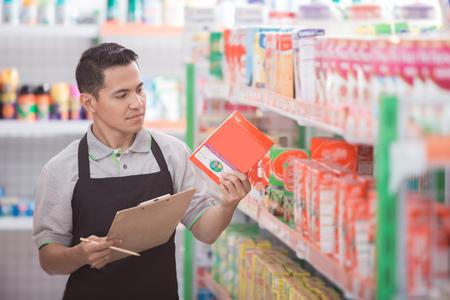 Commerçant masculin vérifiant la qualité du produit au supermarché Banque d'images - 84486498