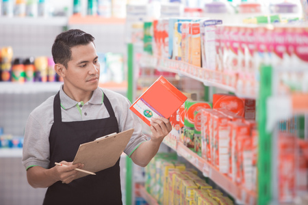 Mężczyzna sklepikarz sprawdzający jakość produktu w supermarkecie Zdjęcie Seryjne
