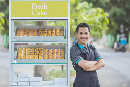 Le propriétaire d'une petite entreprise se tient fièrement devant son stand de nourriture. Concept de nourriture de rue Banque d'images