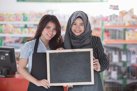店の前に空の黒板に立って 2 人の幸せスーパー スタッフ 写真素材