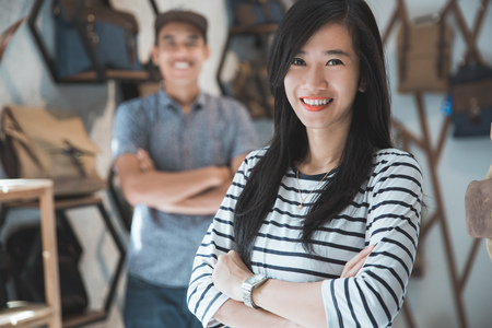 Portret van twee jonge Aziatische zakenbezitters in hun winkel