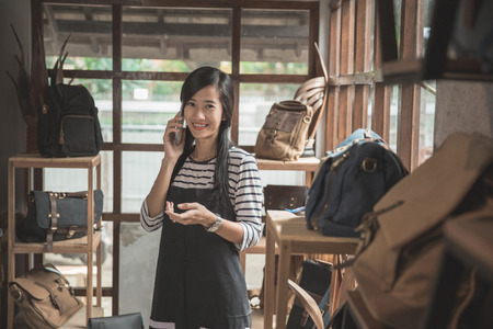 young asian business owner talking to mobile phone in her fashion store Stok Fotoğraf - 84486576