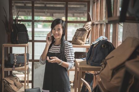 jonge Aziatische ondernemer praten met mobiele telefoon in haar mode winkel