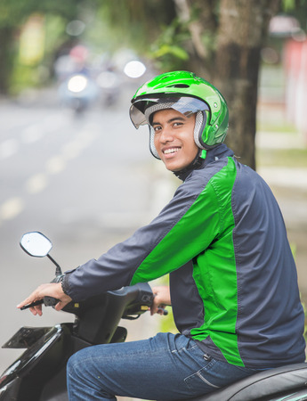 portrait of happy asian man work as a commercial motorcyle driver smile to camera