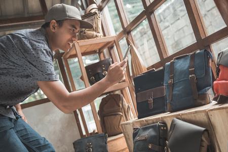 온라인으로 판매하기 위해 그의 가방 제품을 찍는 비즈니스 소유자 스톡 콘텐츠 - 84486589