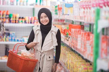 アジアのイスラム教徒の女性のスーパー マーケットでいくつかのハラール商品を購入