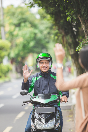 portrait of woman standing on a sidewalk ordering motorcycle taxi by waving her hand 版權商用圖片