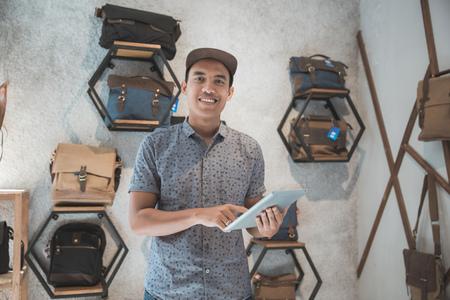 가방 가게에서 태블릿 PC를 사용하는 상점 주인