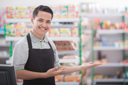 Portret van een lachende winkelier in een supermarkt gastvrije klant Stockfoto