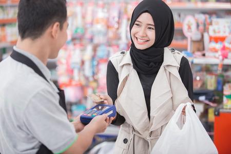 현금없는 지불에 쇼핑. 식료품 가게 또는 신용 카드로 지불 슈퍼마켓에서 음식을 구입하는 행복 한 회교도 여자