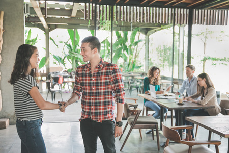 two young creative team shake hand in cafe while meeting