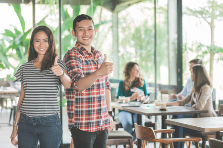 young business meeting in coffee shop. two partner showing thumb up Stock Photo