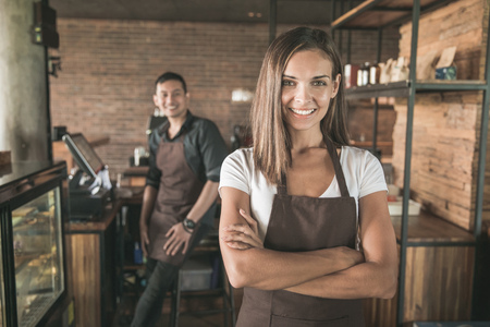 portrait of beautiful mixed race cafe owner smiling proudly in their shop