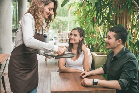 portrait of a female waitress serving coffee to a couple customer