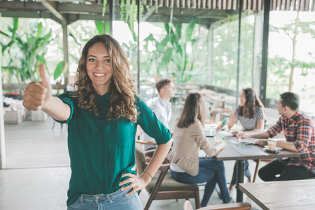 portrait of mixed race attractive young woman showing thumb up after meeting with her teamwork