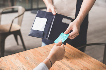 close up of customer hand paying his bills using credit card, assisted by waitress Stock Photo