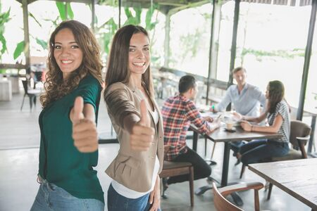 portrait of two mixed race attractive young woman showing thumb up after meeting with her teamwork
