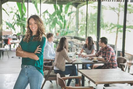 portrait of mixed race attractive young woman smiling while meeting with her team in a cafe