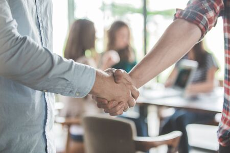 close up of two young male business partner shake hand in a cafe